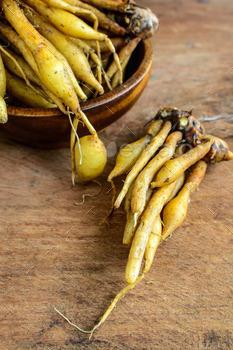 Fresh galingale (Boesenbergia rotunda) on wooden table