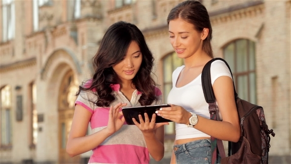 Two Cute Girls Web Surfing On a Tablet