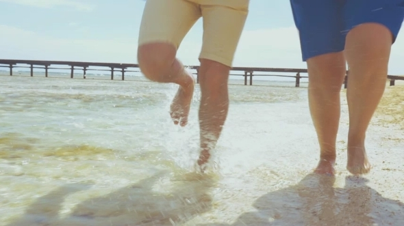 Barefoot Couple Running In Shallow Water