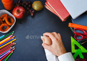 Mans hand holding a childs hand with chalk. School concept