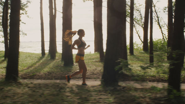 Young Girl is Running in Forest at Morning