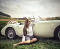 Sensual girl sitting on the grass next to her white car - PhotoDune Item for Sale
