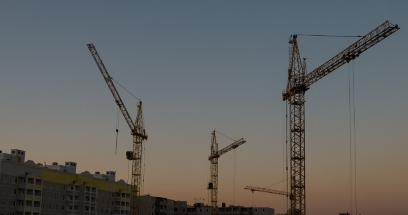 City Construction By Crane At Sunset
