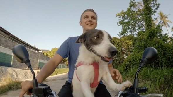 Cheerful Man And Dog Riding The Bike Together