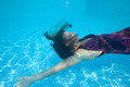 Beautiful woman girl dress underwater diving swim blue sunny day pool
