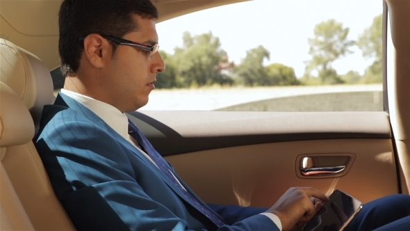 Businessman Sitting In The Car Reading Tablet
