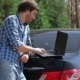 Man Working On The Computer In The Trunk Of Car - VideoHive Item for Sale