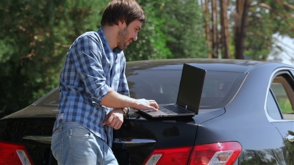 Man Working On The Computer In The Trunk Of Car