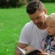 Father And Son Reading Book In Park - VideoHive Item for Sale