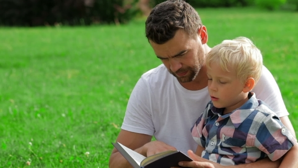 Father And Son Reading Book In Park