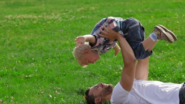 Father And Son Playing On The Grass In Park