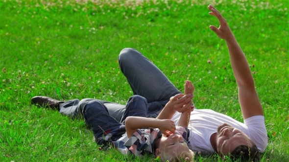 Father And Son Dreaming On The Grass In Park