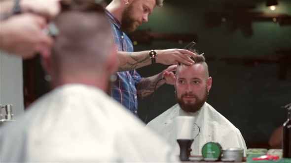 Beard Barber Making Haircut To Hipster Client