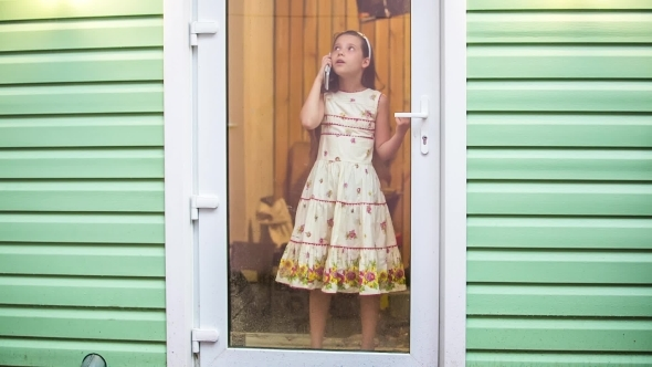 Cute Girl Standing At Door And Talking On