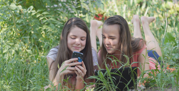 Two Teenage Girls Using Notebook And Smartphone