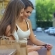 Two Girls On a Bench Looking At The Phone - VideoHive Item for Sale