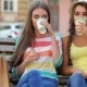 Two Girls On a Bench Drinking Coffee - VideoHive Item for Sale