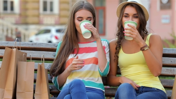 Two Girls On a Bench Drinking Coffee