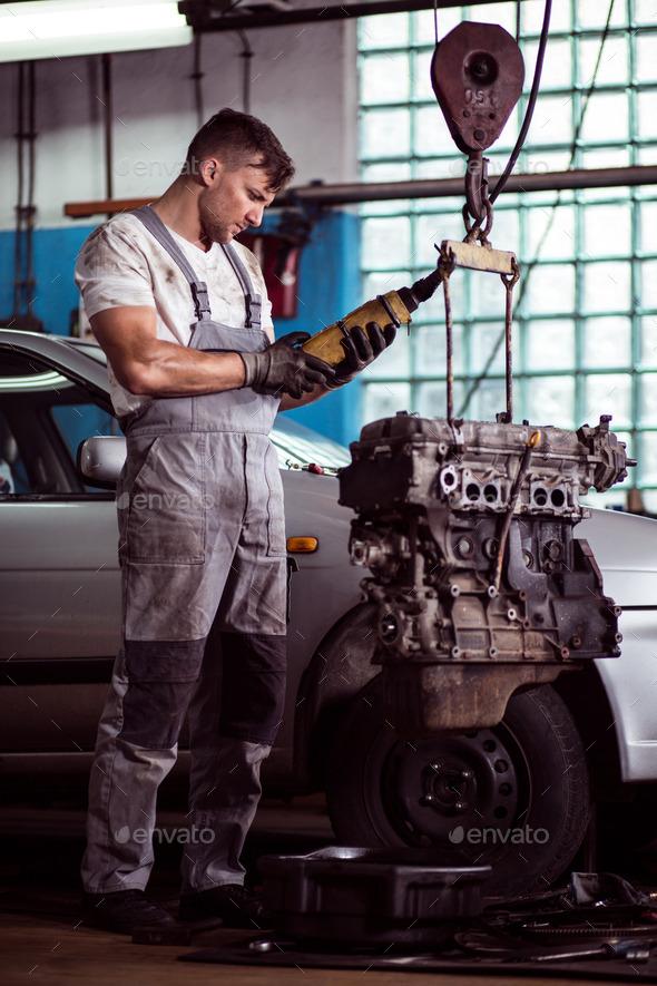 Auto mechanic inspecting motor car - Stock Photo - Images