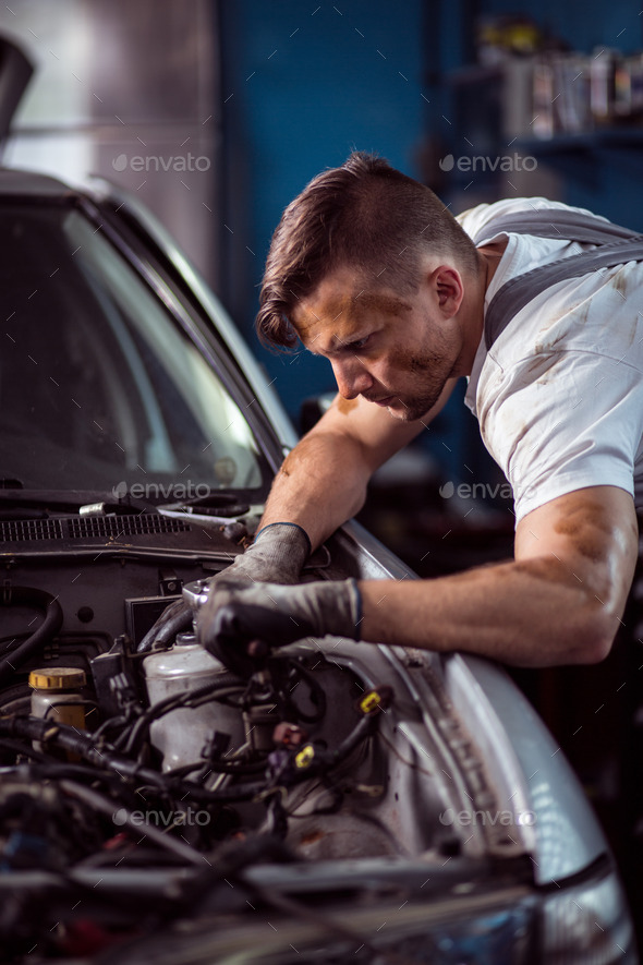 Young handsome man servicing vehicle - Stock Photo - Images