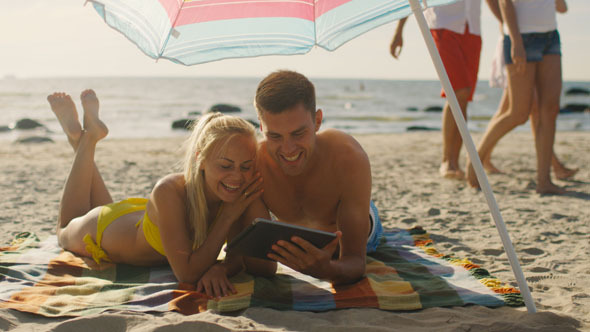 Couple is Using Tablet PC on the Beach