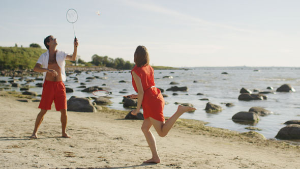 Man and Girl are Playing in Badminton on the Beach
