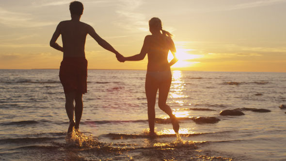 Couple is Running into Water in Sunset Light