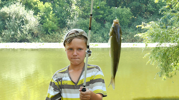 Young Caucasian Boy With Fishing Pole And Fish
