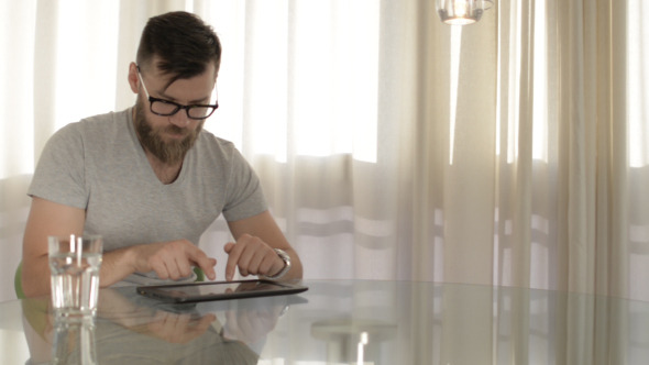 Young Man Typing on Tablet