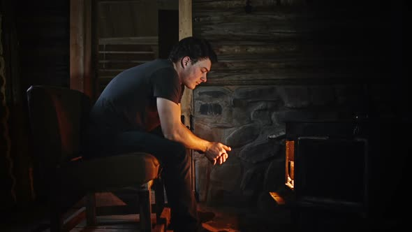 Man Warming In Front Of Slow Burning Stove