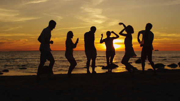 Young People are Dancing on the Beach at Sunset 3