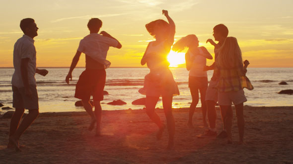 Young People are Dancing on the Beach at Sunset 4