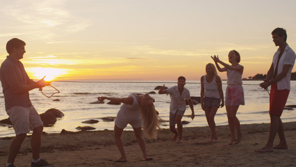 Young People Having Fun on the Beach at Sunset