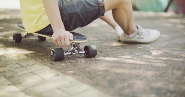 Man Sitting On His Skateboard