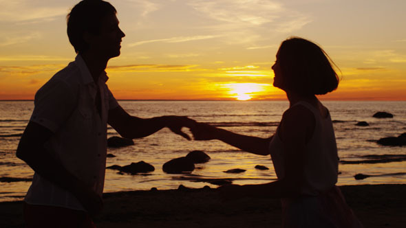 Couple is Dancing on the Beach in Sunset Time