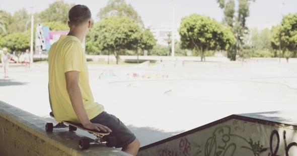 Man Sitting On a Skateboard Balanced On a Wall