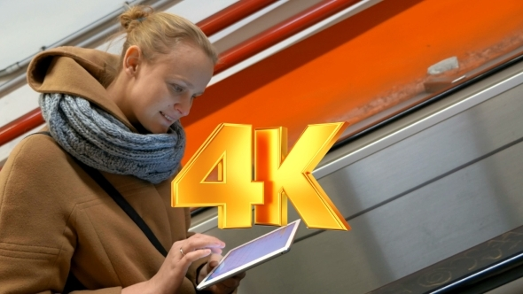 Woman On Escalator Using Tablet Computer