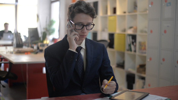Young Man Busy on Phone in Office