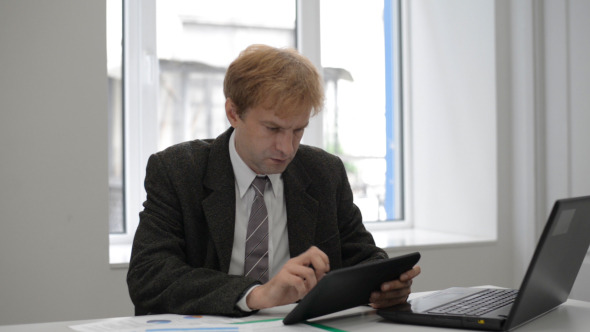 Businessman Typing on Tablet