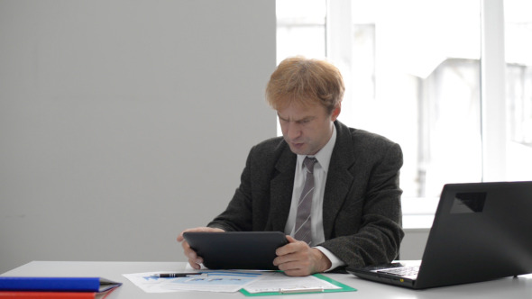 Anxious Businessman Using Tablet at Work