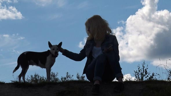Girl and Dog on the Background of Sky
