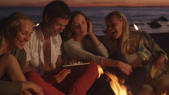 Group of People near Campfire using Tablet PC
