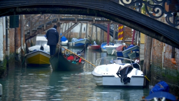 Gondola Sailing Along The Water Canal In Venice