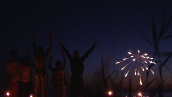 Group of Friends Watching Fireworks on the Beach