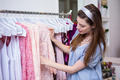 Brunette woman shopping for clothes in fashion boutique