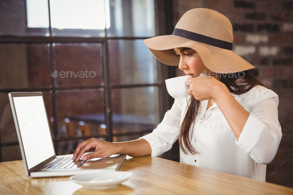 A businesswoman using her laptop while enjoying a coffee in a cafe - Stock Photo - Images