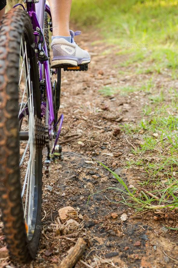 Close up view of woman pedaling on mountain bike in the nature - Stock Photo - Images
