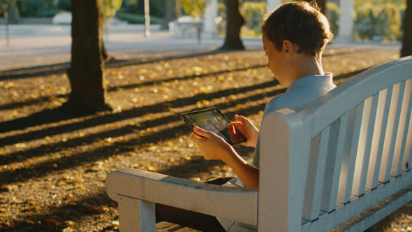 Boy is Sitting at Park and Using Tablet PC 3
