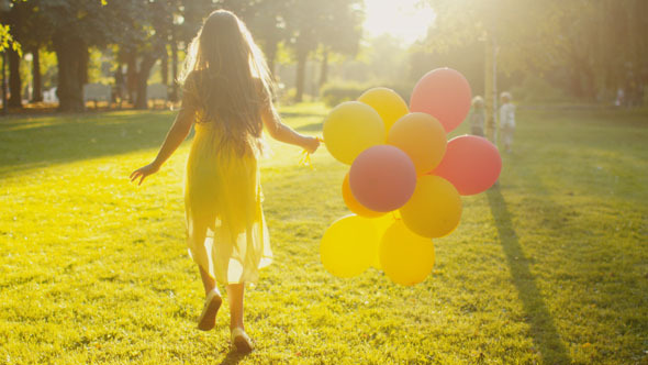 Girl is Running at Park with Balloons in Hand