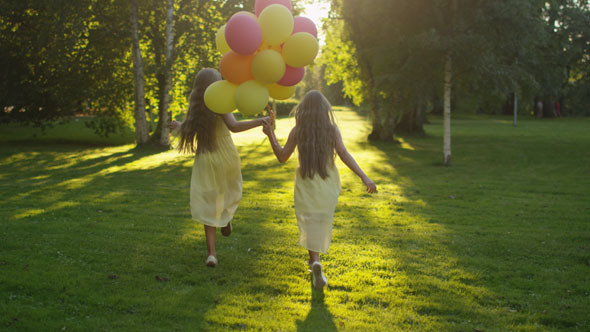 Twin Girls is Running at Park with Balloons in Hand